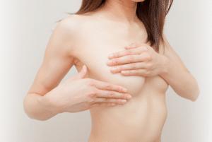 Medisch Cosmetica - beeld website Permanent Mooi van Janny Hanegraaf, vrouw met ontbloot bovenlijf, hand op borst