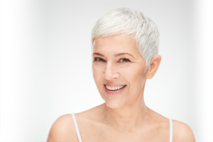 Beeld van een vrouw, lacht, kort grijs haar, een beeld van Permanent Mooi, Janny Hanegraaf